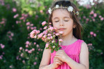 Close portrait of beautiful little girl with roses flowers